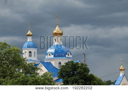 top of the orthodox church sink in deep green of trees before the storm