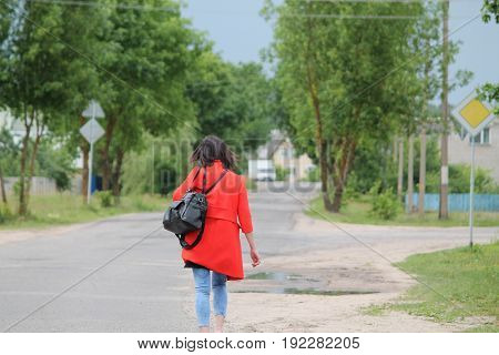 young woman in red coat walk on green summer street