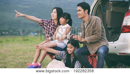 Happy little girl e with asian family sitting in the car for enjoying road trip and summer vacation in camper van