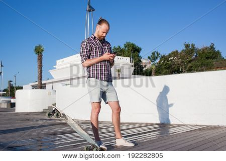 ypung bearded skater with cellphone, summer park background