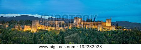 Panorama of Alhambra - medieval Moorish fortress surrounded by yellow autumn trees illuminated in the evening Granada Andalusia Spain
