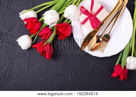 Festive table setting. White plate golden cutlery box with present and white and red tulips flowers on black textured backgroud. Selective focus. Top view. Place for text.