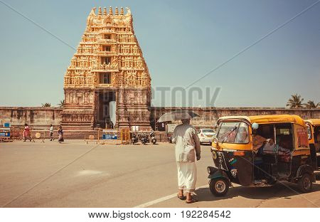 BELUR, INDIA - FEB 23, 2017: Man walking to 12th century Chennakeshava Temple with carved tower gopuram on February 23, 2017. Population of Karnataka state is 62,000,000 people