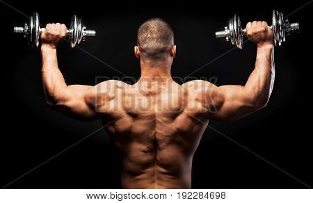 Man with dumbbells back view black background