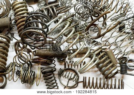 Close up of metal springs and coils on white background