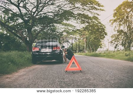 Stressed man sitting after a car breakdown with Red triangle of a car on the road
