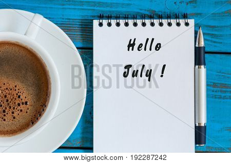 Hello July on Notebook with morning cup of coffee.
