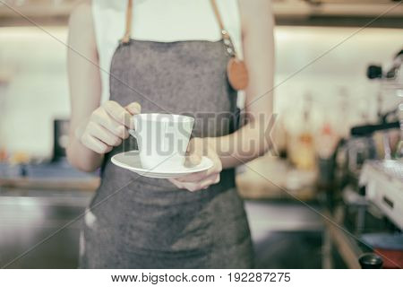 Asian women Barista holding a cup of coffee - Working woman small business owner food and drink cafe concept
