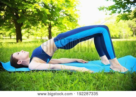 Fitness scene close-up. White girl in blue sportswear does stretching outdoors. Brunette girl does yoga on green grass.