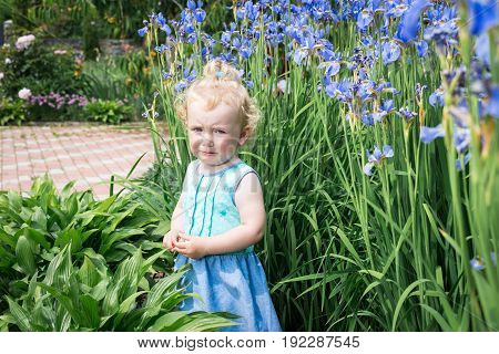 Little girl is crying and very sad. Girl is standing in the flower garden.
