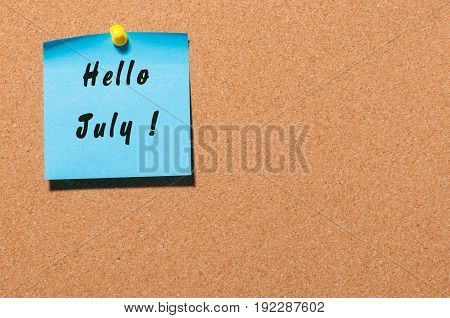 Hello July on blue sticker pinned to corc noticeboard with empty space for text.