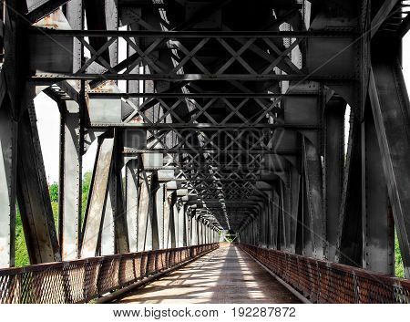 A road under an old steel railway bridge with a pattern of iron beams dappled with sunlight