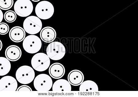 Group of buttons for clothing on a black background.
