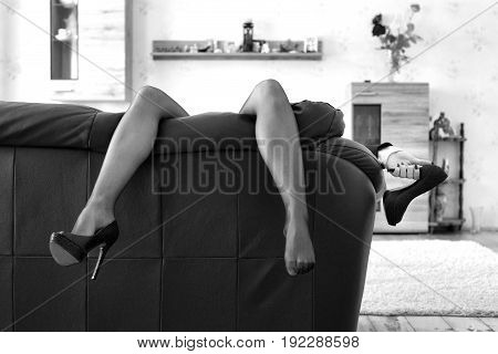 Businesswoman hanging sexy long legs at home on sofa after workday holding high heels black and white