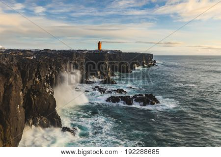 Lighthouse over the cliff ocean seashore in Iceland. Long exposure panoramic photo of waves splashing on the rocks on a cloudy day. Nature and wilderness concepts.