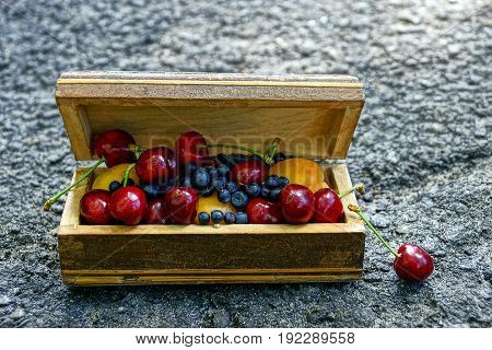 Ripe fruit in a wooden casket on a gray asphalt
