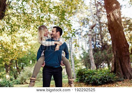 Handsome man giving his beautful girlfriend piggyback in park