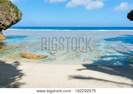 Tropical patterns and colors of coral reef sea and sky from islated beach framed by shadow and rock coastal features