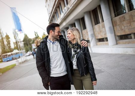 Young cute couple in love walking together on street