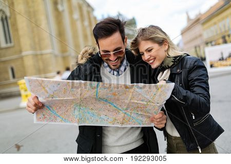 Smiling young attractive couple looking at map on street