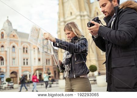 Young cute attractive happy couple enjoying city as tourists