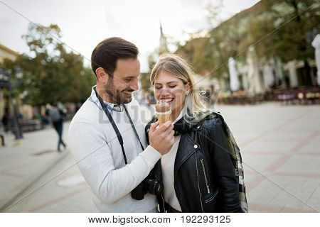 Romantic young attractive couple sharing ice cream on street