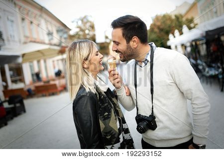 Happy young couple eating ice cream together on street