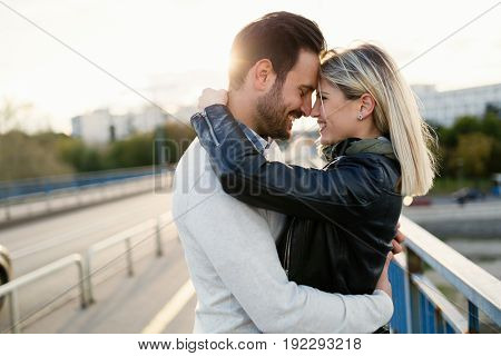Happy young couple hugging and kissing each other on bridge