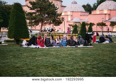 Istanbul, June 16, 2017: Many people of the Islamic religion take food on the Sultanahmet square next to the blue mosque along with their relatives at the time allowed in the Ramadan fast.