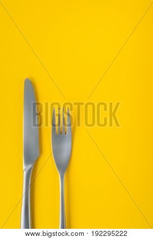 Fork and knife on yellow background sparse composition with copy space. Dinner theme template and background