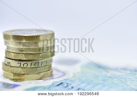 Coins stacked on paper money against white background