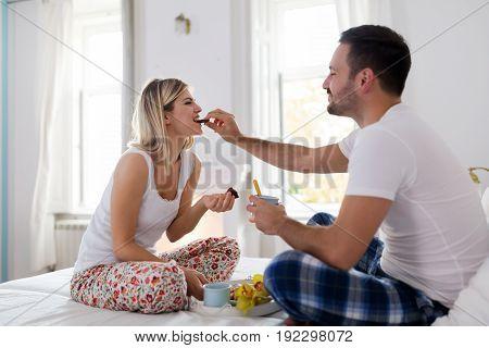 Romantic young happy couple having breakfast in bed