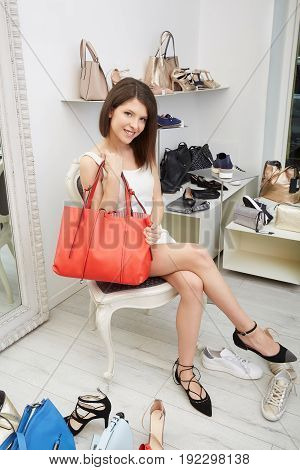 full body portrait of elegant woman sitting next to shopping bags and pairs of shoes