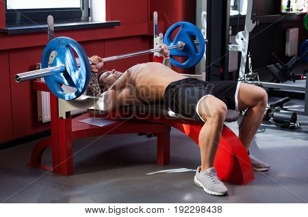 Bodybuilder man with naked torso performing bench press with a barbell at the gym
