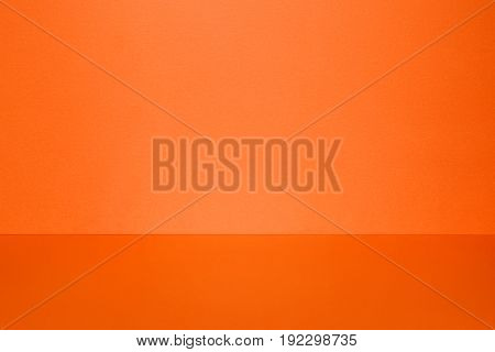 Clear empty orange studio space. Wall and floor with light spot. Interior background and template