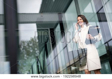Beautiful and attractive businesswoman talking on cellphone standing