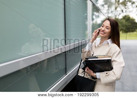 Attractive and beautiful businesswoman standing and taking call