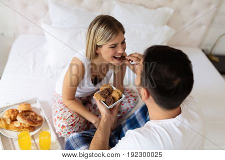 Romantic young couple having breakfast sitting on bed