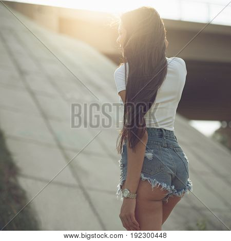 A young slender girl walks near a bridge in the rays of the summer sun.