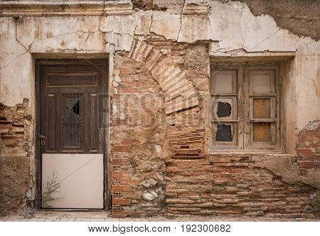 ancient wooden door and a window on a wall made of bricks