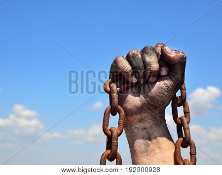 Rusty iron chain in human male right hand against the blue sky