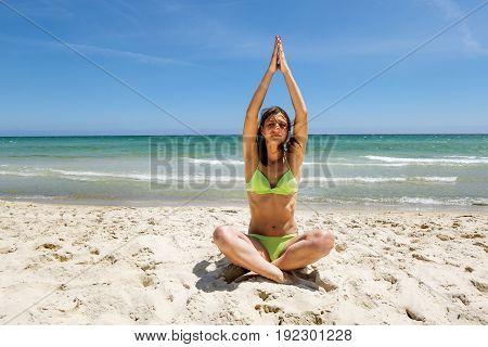 Tanned girl in bikini doing yoga on the Sunny sea beach