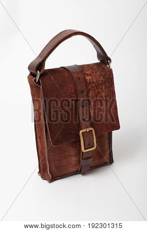 Antique leather bag of suede with buckle of brass on a white background