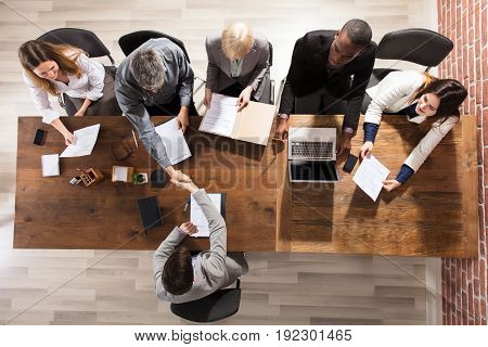 Overhead View Of Business Partner Shaking Their Hands In Meeting