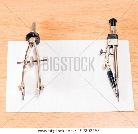 Two compasses for drawing on a piece of paper with a drawn circle useful tools for work and education
