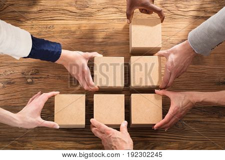 Businesspeople Holding A Block To Complete Growth Bar Graph On Desk