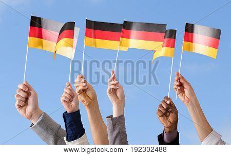Hands Holding German Flag Against Blue Sky