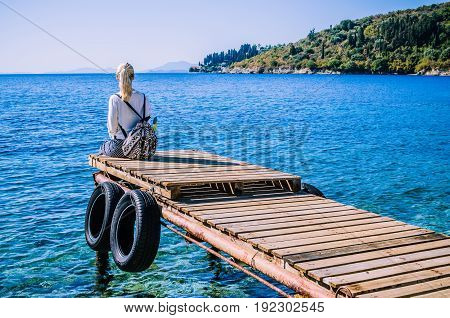 Girl with backpack on pier on the beach near Kalami looking into sea. Corfu Island, Greece.