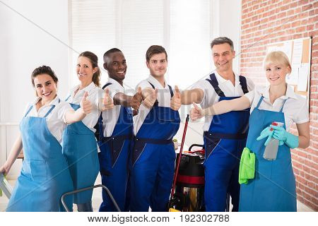 Happy Diverse Janitors In The Office With Cleaning Equipments Showing Thumb Up Sign
