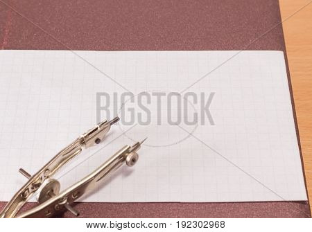 Tool for drawing a pair of compasses on a sheet of paper with a drawn circle on a background of a brown hard cover of a diary